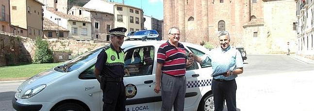 Juan José Álvarez, en el centro, con el jefe de la Policía Local, durante la entrega de un coche patrulla.
